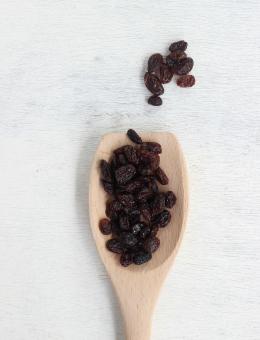 A wooden spoon of Black Raisins