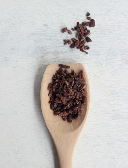 A wooden spoon of Cocoa Nibs