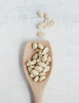 A wooden spoon of shelled Peanuts