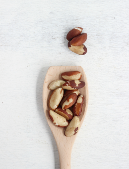 A wooden spoon of Raw Brazil Nuts