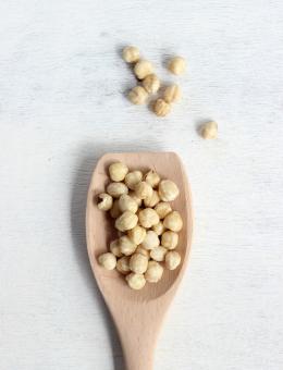 A wooden spoon of shelled Raw Hazelnuts