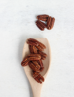 A wooden spoon of Raw Pecans