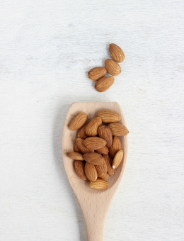 A wooden spoon of Whole Raw Almonds