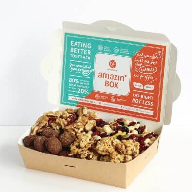 Green and orange Amazin'Box, eating better together, eat right not less, you are what you eat, fuel your body with the best that nature has to offer, with granolas, cookies, walnuts, cranberries, cashews, peanuts, raisin