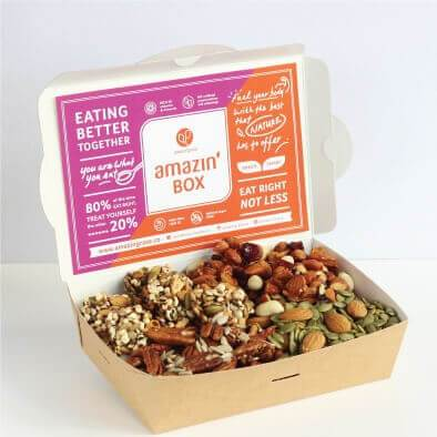 Purple and orange Amazin'Box, eating better together, eat right not less, you are what you eat, fuel your body with the best that nature has to offer, with rosemary pepitas seed, almonds, pecans and five spice tamari