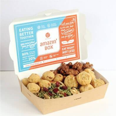Blue and orange Amazin'Box, eating better together, eat right not less, you are what you eat, fuel your body with the best that nature has to offer, with cashew cookies, berry-licious and zesty maple glazed nut mixes