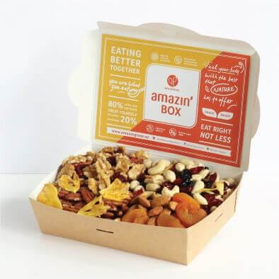 Yellow and orange Amazin'Box, eating better together, eat right not less, you are what you eat, fuel your body with the best that nature has to offer, with pecans, walnuts, cashews, raisins, cranberries, almonds, apricots, pineapple.