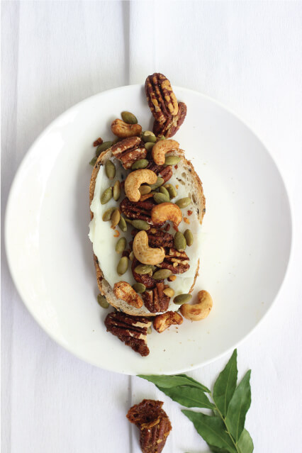 Amazin'graze Coconut curry lime on cream spread on a piece of bread, with cashews, pecans and pepita seeds.