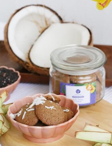 Pulut Hitam Cookies in a pink bowl with fresh coconut, black glutinous rice, and a jar of Pulut Hitam Cookies in the background