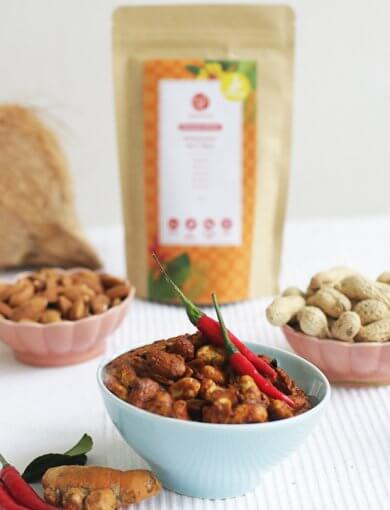 Rendang Spice Nut Mix in bowl with fresh chilis, ginger, almonds, peanuts, and a packet of Rendang Spice Nut Mix packaging in the background