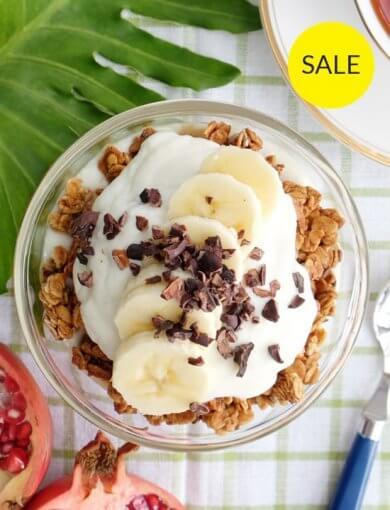 Banana Split Yogurt Parfait - top down image of granola and yogurt parfait sprinkled with cacao nibs and banana slices