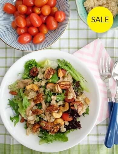 Protein Power Salad Bowl - top down image of salad greens with nuts, cherry tomatoes, and almond butter dressing